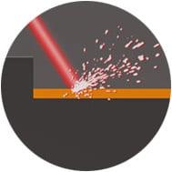 Laser trifft auf Oberfläche bei Gravur